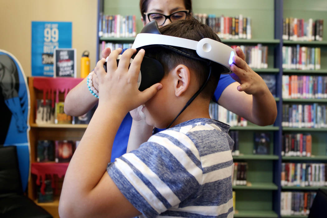Senior youth service specialist Andrea Daciuk, Las Vegas, helps puts on VR goggles on Dominic G ...