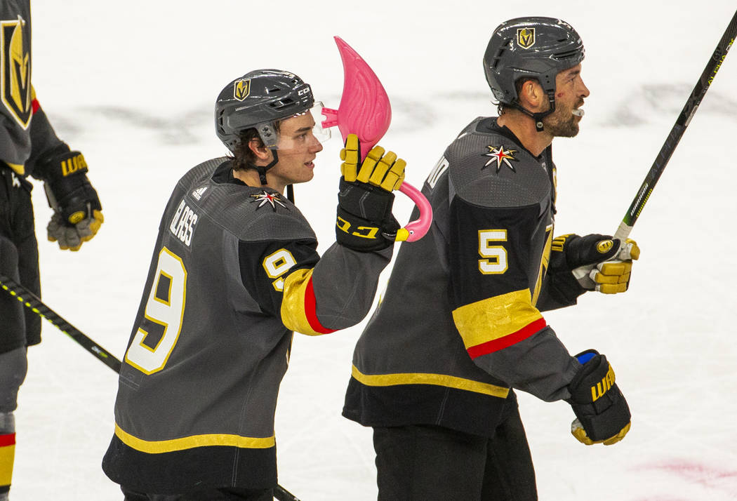 Vegas Golden Knights center Cody Glass (9) receives a pink flamingo and skates with teammate de ...