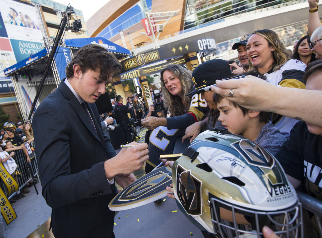 Golden Knights' Cody Glass signs autographs on the gold carpet after arriving for the NHL seaso ...
