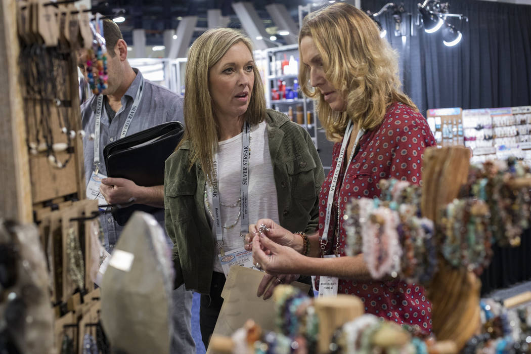 Lynn Mitchell, left, of Cape Cod, looks at gem stones and jewelry for sale next to colleague Ka ...