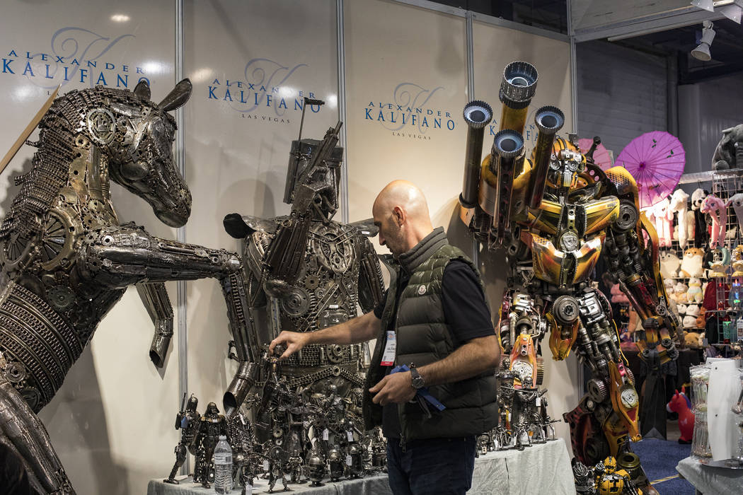 Alex Kalifano rearranges metal sculptures at his booth at the Souvenir & Resort Gift Show a ...