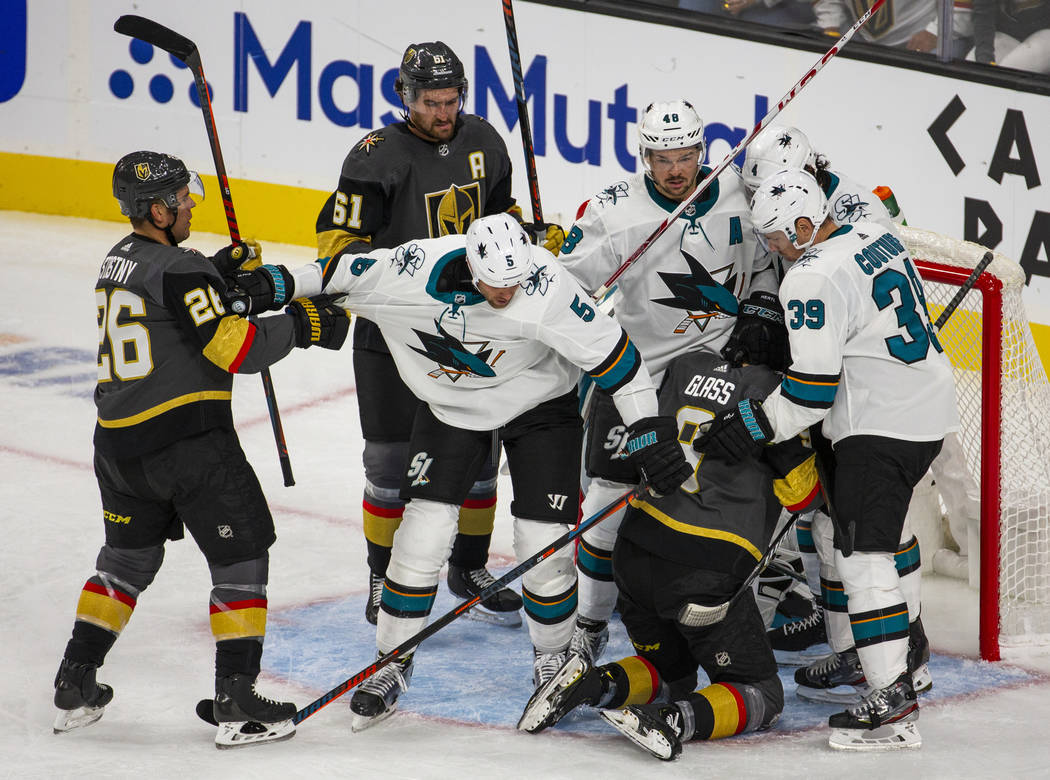 Vegas Golden Knights and San Jose Sharks players fight at the net after a near goal by Vegas Go ...