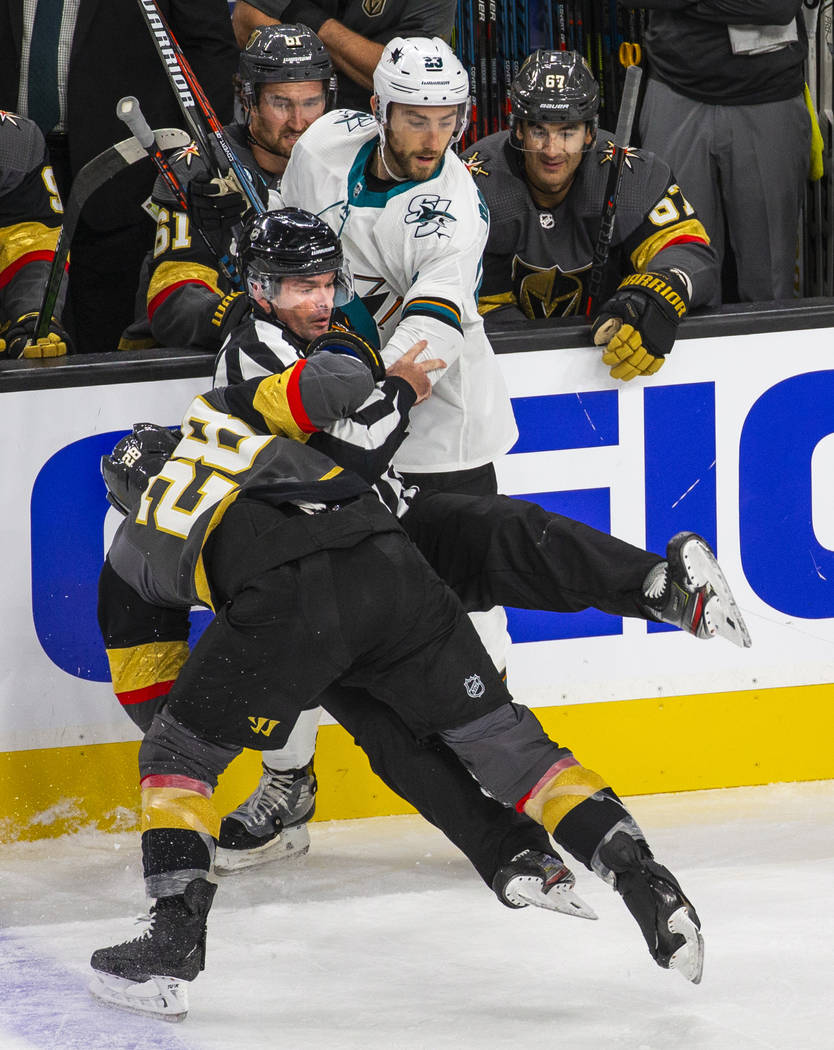 Vegas Golden Knights left wing William Carrier (28, below) and San Jose Sharks right wing Barcl ...