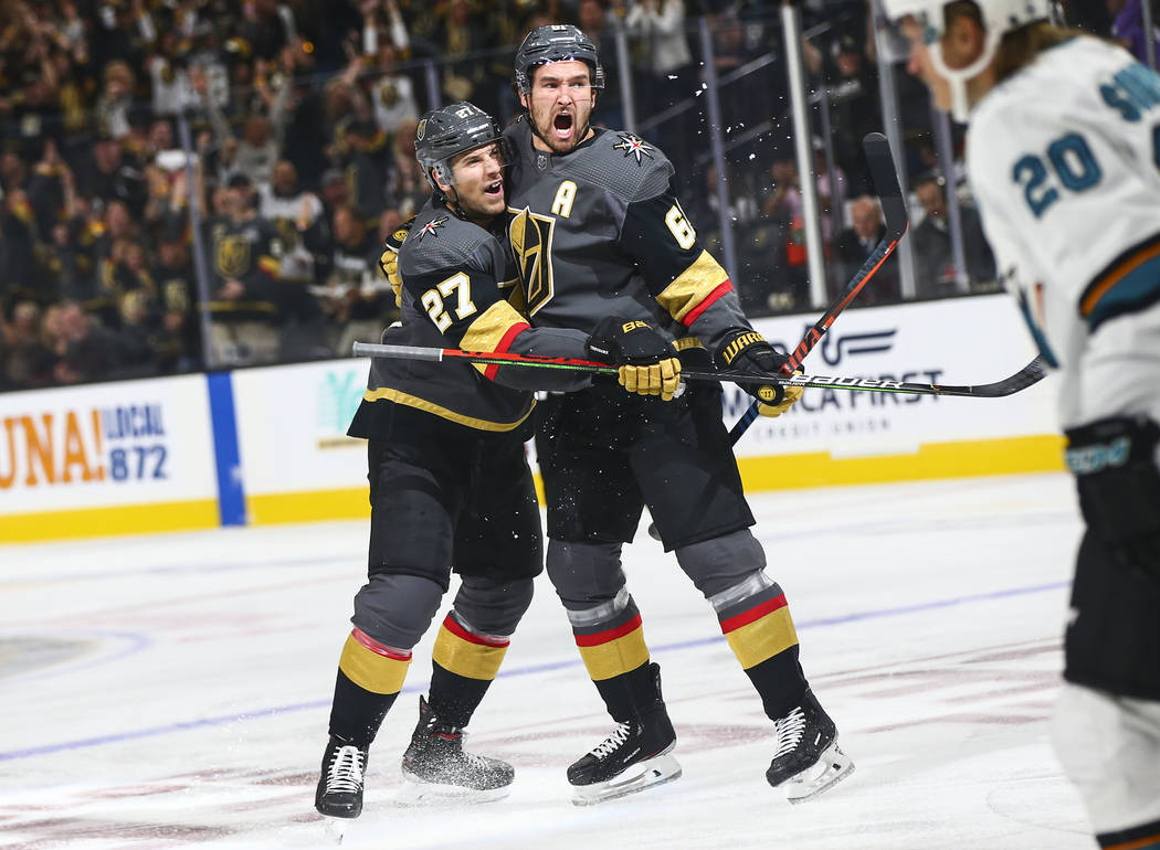 Golden Knights' Mark Stone, right, celebrates his goal with Shea Theodore (27) during the first ...