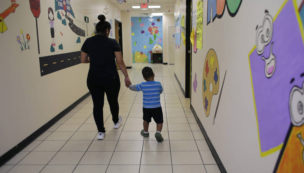 "A young migrant boy walks with a Comprehensive Health Services caregiver at a ""tender-age& ..."