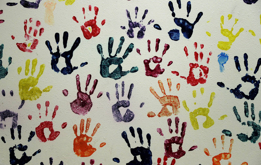 "Hand prints representing migrant children line a hall at a ""tender-age"" facility for ..."