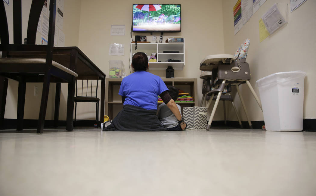 "A Comprehensive Health Services caregiver watches TV with a young migrant at a ""tender-age ..."