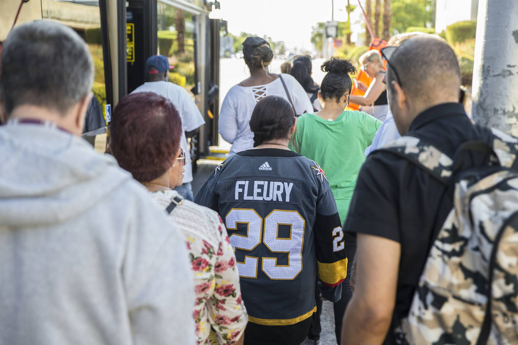 Elena Leger, middle, waits in line to board an RTC bus to Toshiba Plaza to watch the Vegas Gold ...