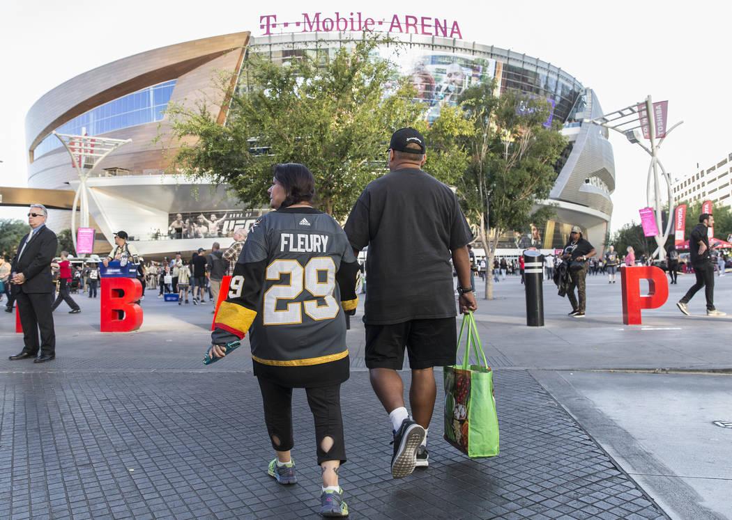 Elena Leger, left, holds hands with boyfriend Fernando Agundez as they walk towards T-Mobile Ar ...