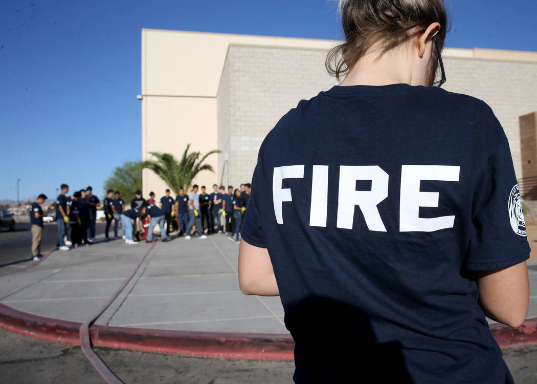 Bonanza High School Fire Science Academy junior Dorothy Elliott attaches a nozzle to a fire hos ...