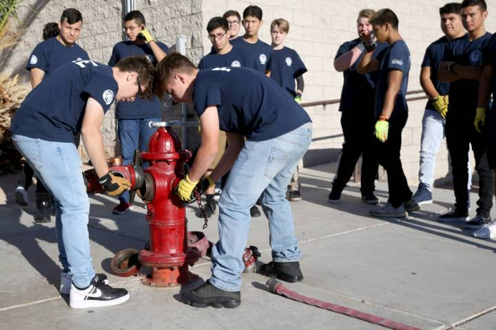 Bonanza High School Fire Science Academy juniors Carlos Olguin, left, and Noah Nason prepare to ...
