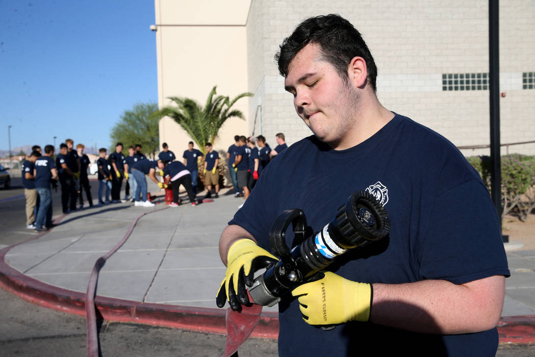Bonanza High School Fire Science Academy junior Angelo Sanchez attaches a nozzle to a fire hose ...