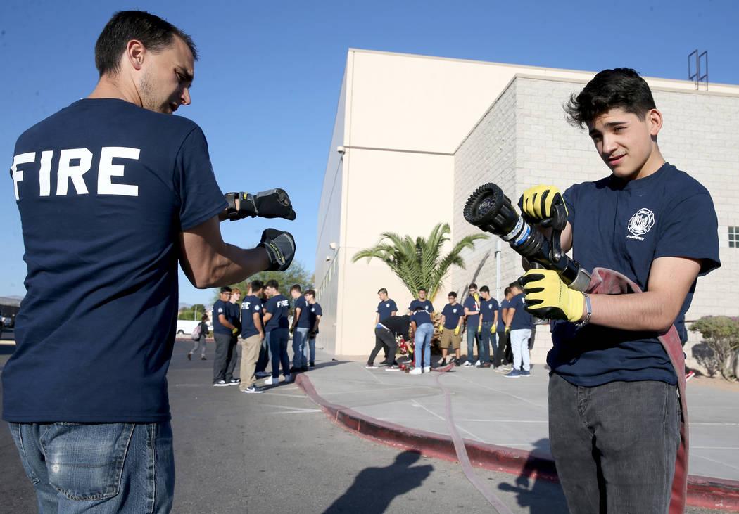 Bonanza High School Fire Science Academy teacher Chris Batterman shows junior Enrique Flores ho ...