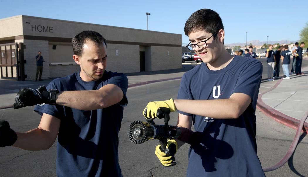 Bonanza High School Fire Science Academy teacher Chris Batterman shows junior Josh Silva how to ...