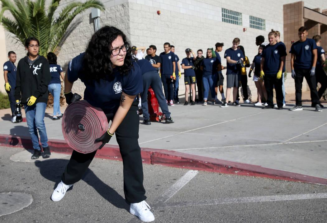 Bonanza High School Fire Science Academy student Julie Mendez rolls out a hose during fire cert ...