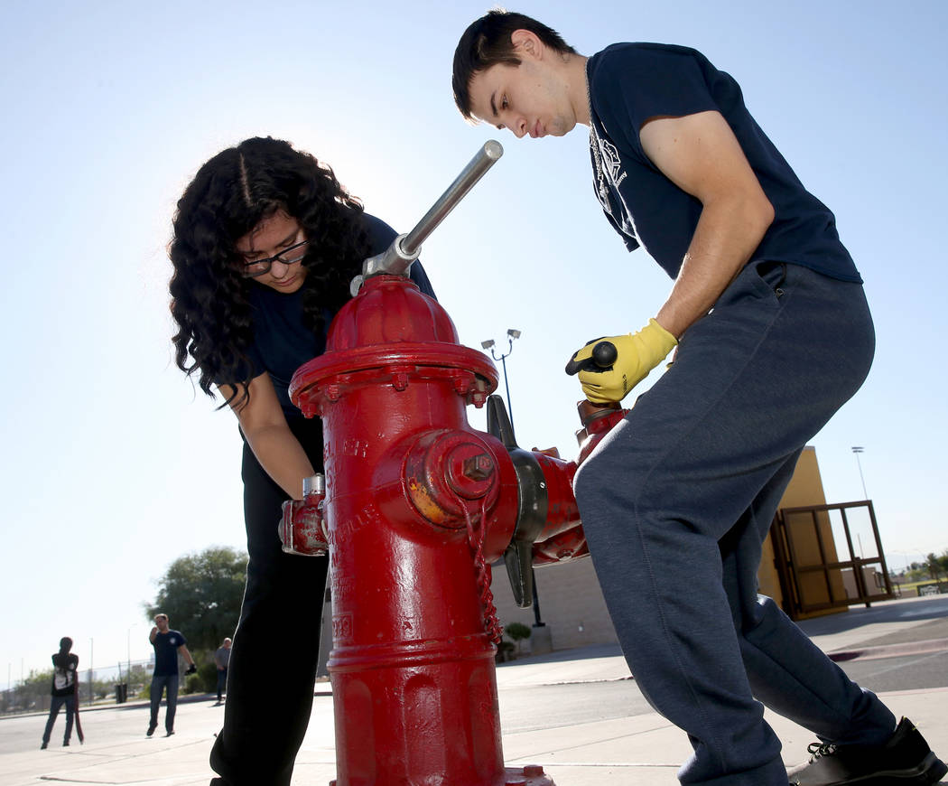 Bonanza High School Fire Science Academy student Julie Mendez and Jacob Perez hook a hose up to ...