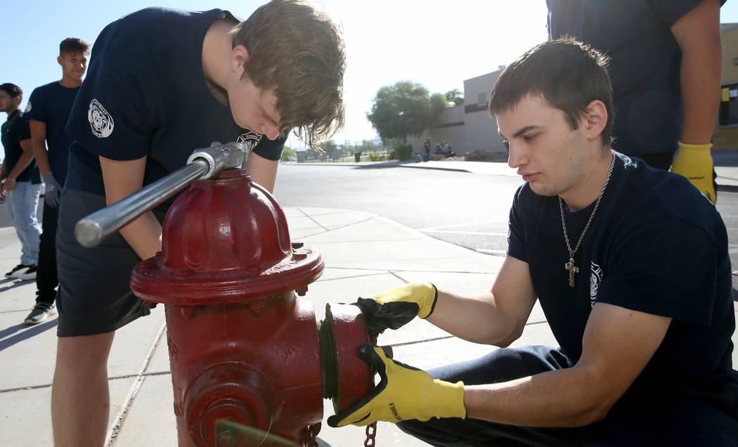 Bonanza High School Fire Science Academy students Charlie Stromoski, left, and Jacob Perez hook ...