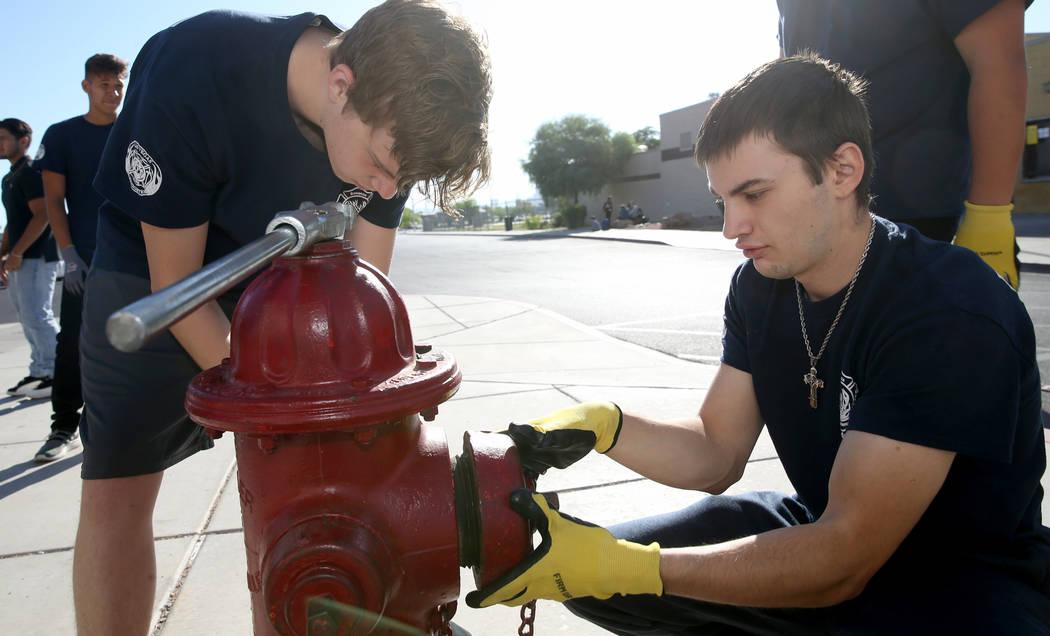 Bonanza High School Fire Science Academy students Charlie Stromoski, left, and Jacob Perez hook ...