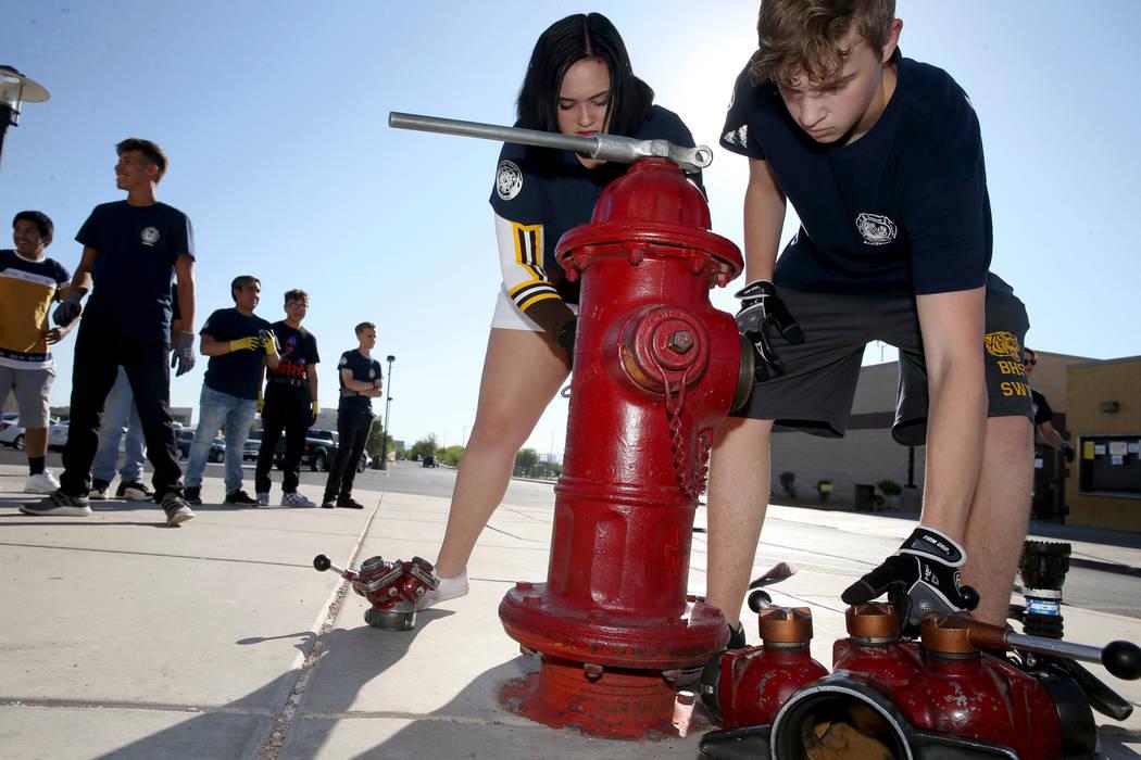 Bonanza High School Fire Science Academy seniors Madi Hornbrook and Charlie Stromoski hook a ho ...