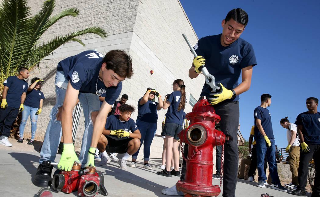 Bonanza High School Fire Science Academy seniors Jerry Galaviz, left, and Angel Corona hook a h ...