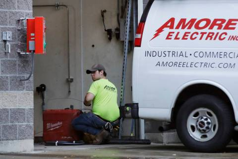 In a Wednesday, Oct. 2, 2019, photo, an electrician works at a car wash in North Andover, Mass. ...