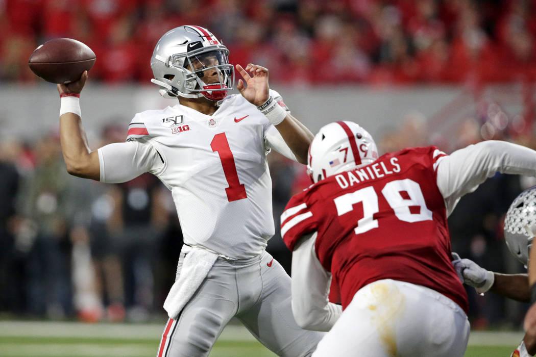 Ohio State quarterback Justin Fields (1) throws a pass as Nebraska defensive lineman Darrion Da ...