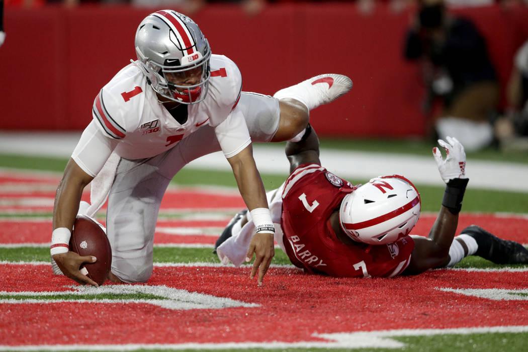 Ohio State quarterback Justin Fields (1) scores a touchdown next to Nebraska linebacker Mohamed ...