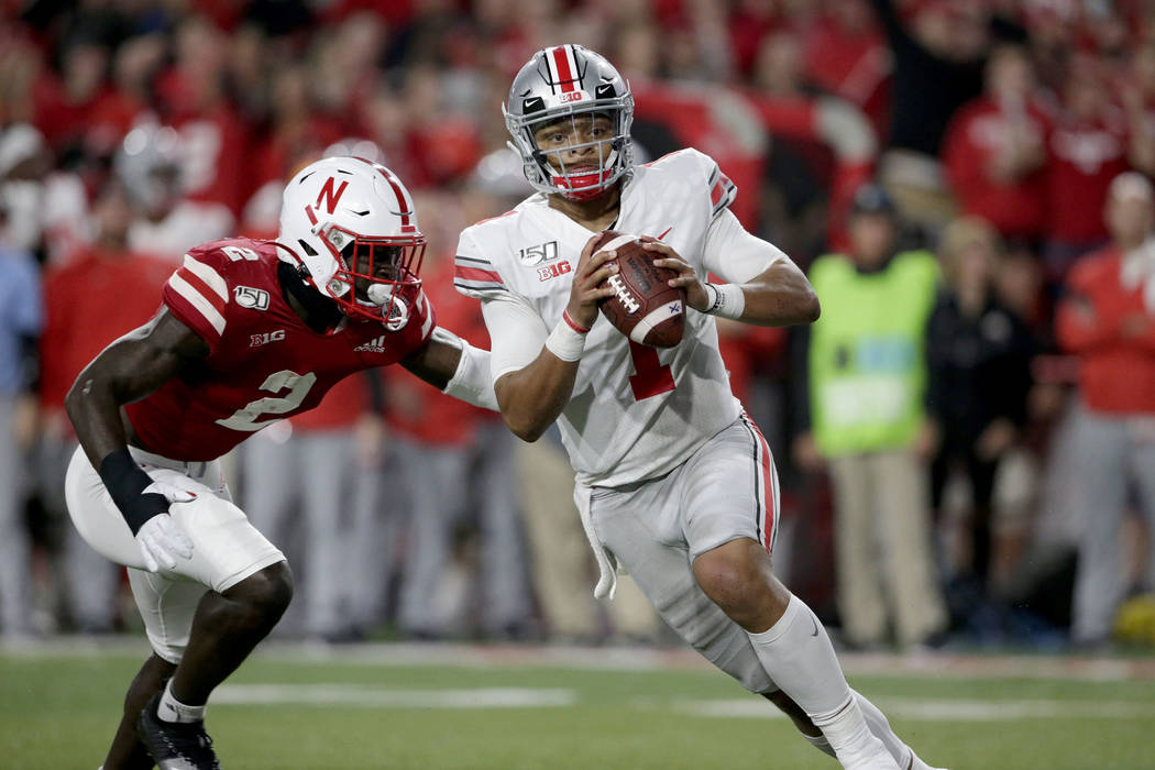 Ohio State quarterback Justin Fields (1) scrambles away from Nebraska linebacker Caleb Tannor ( ...