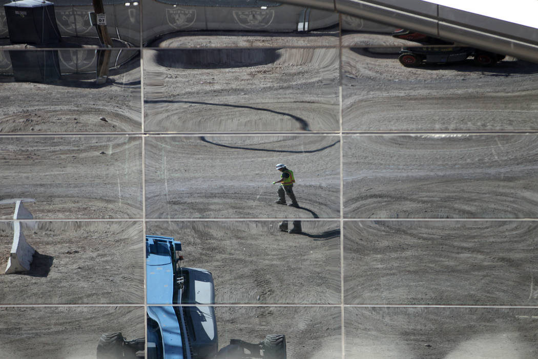 A construction reflects on glass installed at the Raiders Allegiant Stadium in Las Vegas, Thur ...