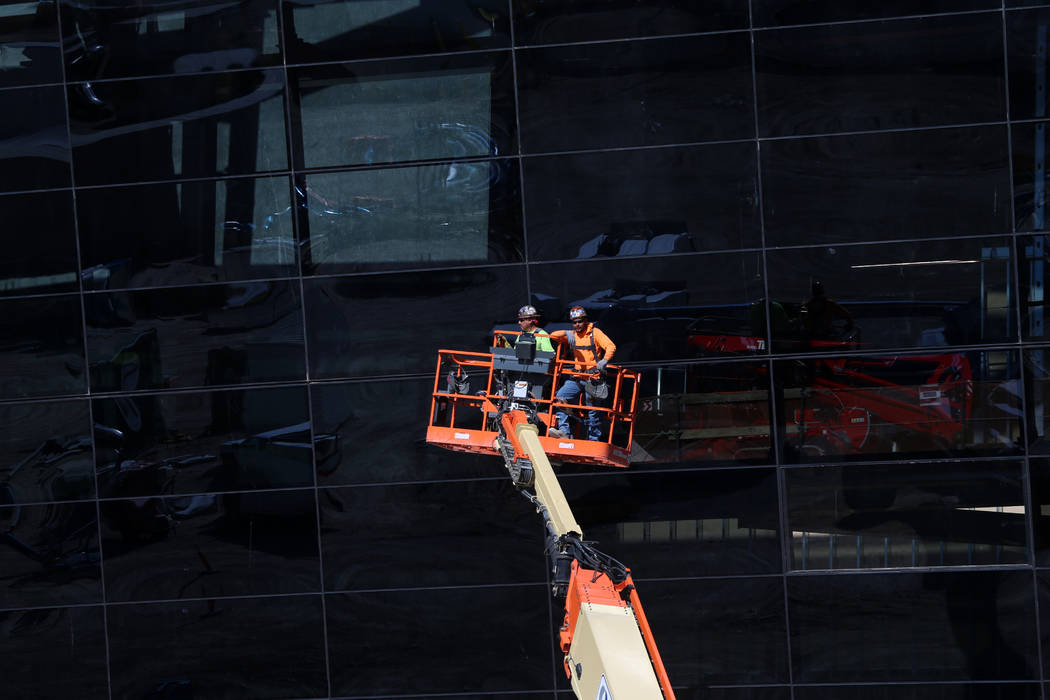 Workers go up on a construction lift at the Raiders Allegiant Stadium in Las Vegas, Thursday, O ...