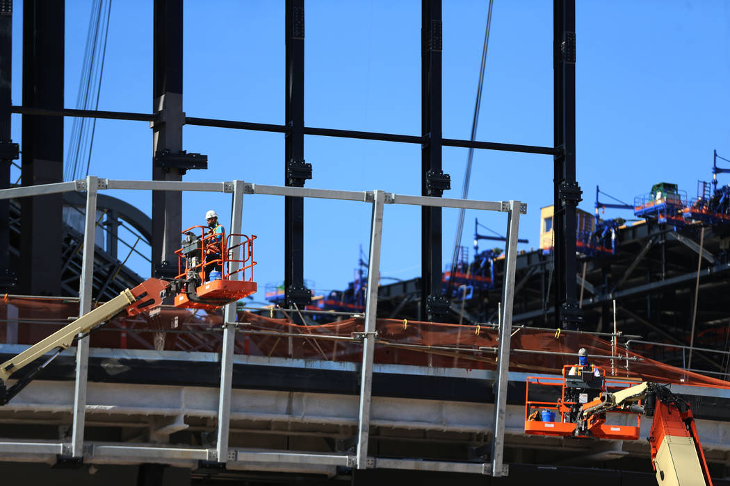 Workers stand on lifts at the Raiders Allegiant Stadium construction site in Las Vegas, Thursda ...