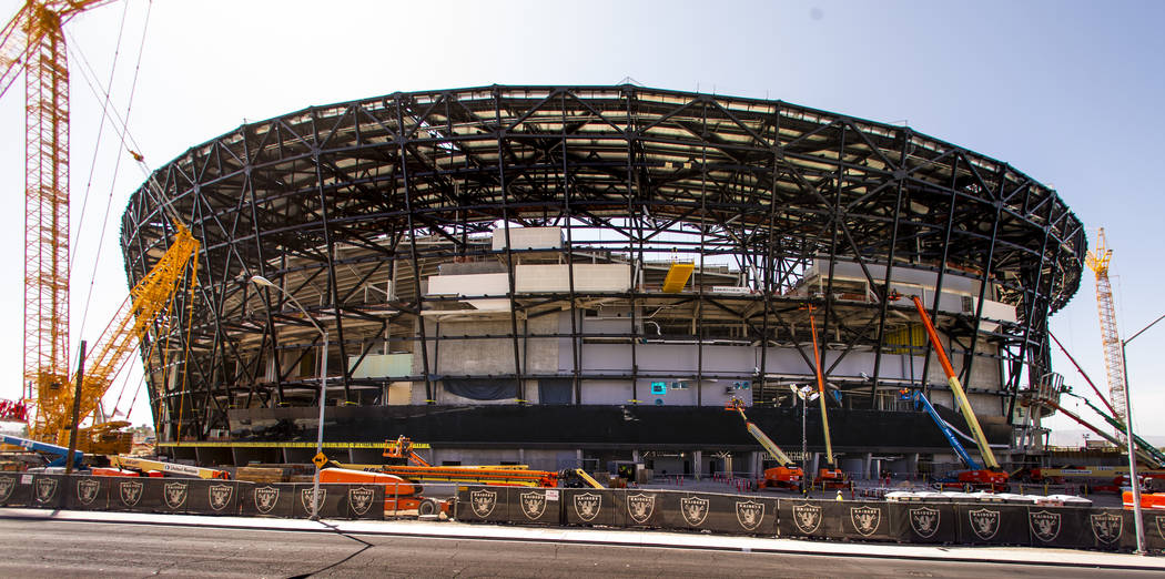Crews work to install glass panes along the lower lever of Allegiant Stadium on Tuesday, Sept. ...