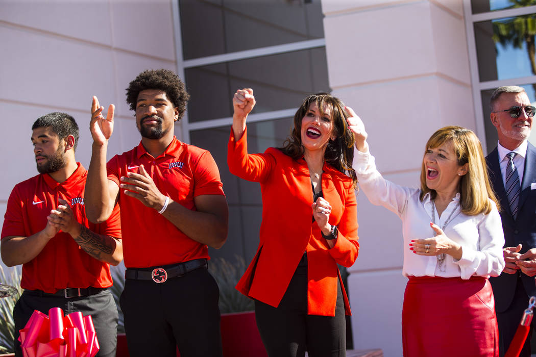 UNLV football players, from left, Giovanni Fauolo, and Armani Rogers cheer alongside UNLV athle ...