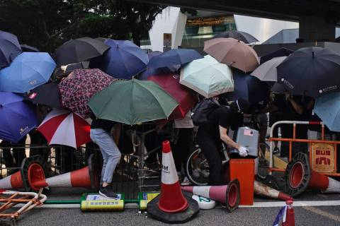 Protesters hide behind umbrellas as they form a barricade to block a road in Hong Kong on Frida ...