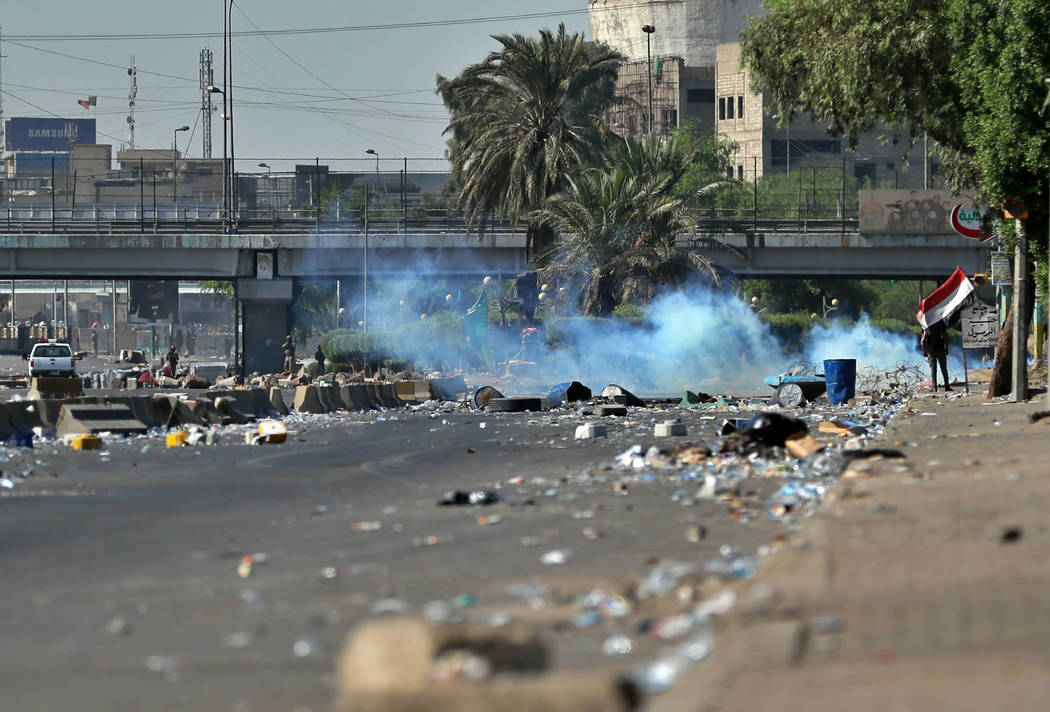 Iraqi security forces fire tear gas while anti-government protesters gather for a demonstration ...