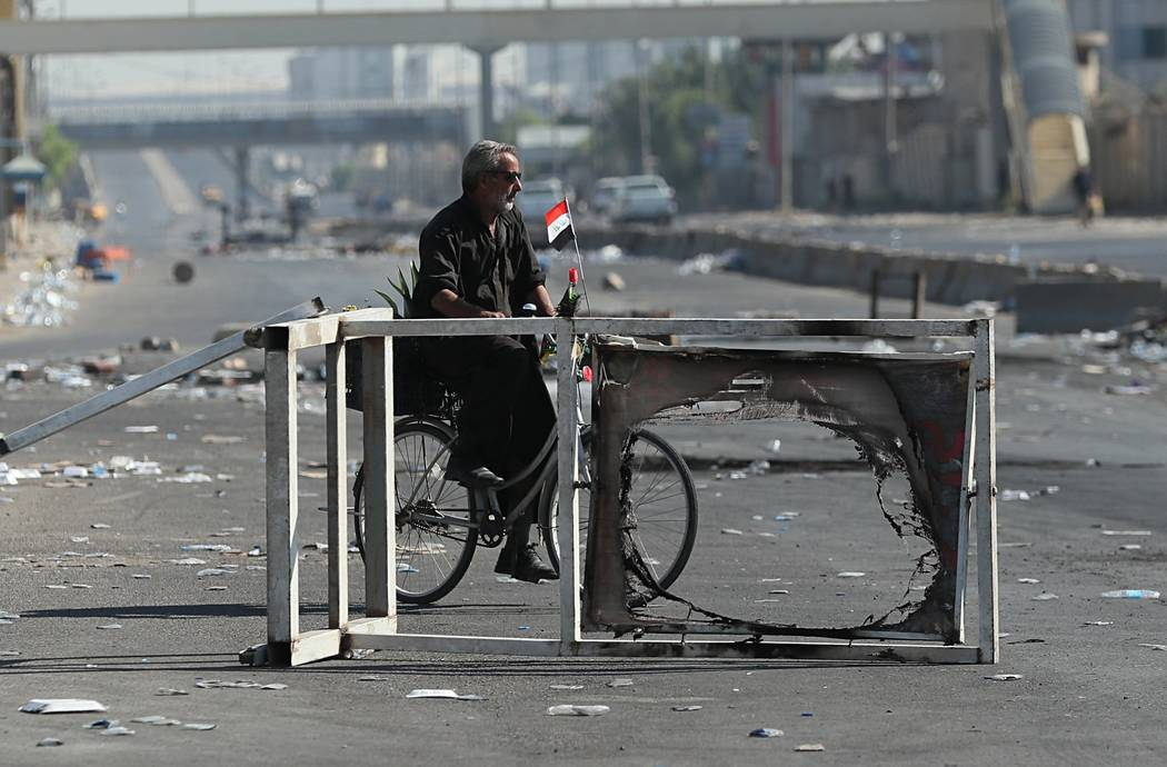 A man rides a bicycle in the protest site area in Baghdad, Iraq, Friday, Oct. 4, 2019. Iraq's p ...