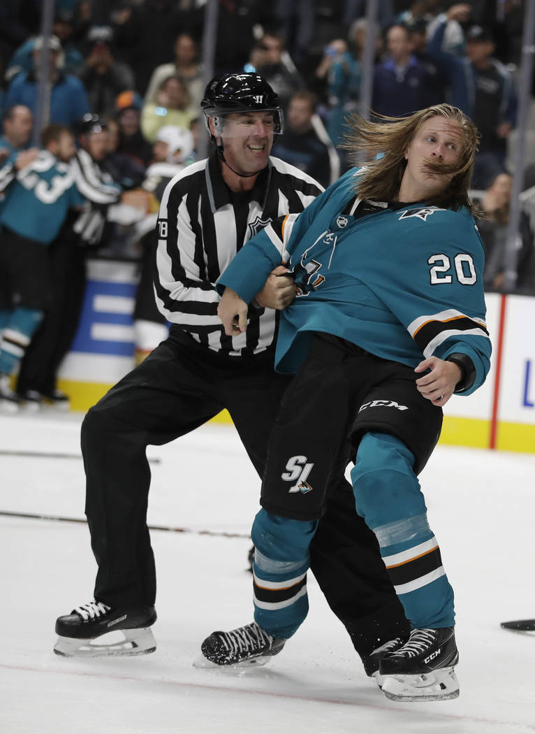 Linesman Brian Mach, left, restrains San Jose Sharks' Marcus Sorensen during a fight in the thi ...