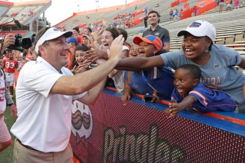 Florida head coach Dan Mullen high fives fans as he leaves the field after defeating Towson in ...