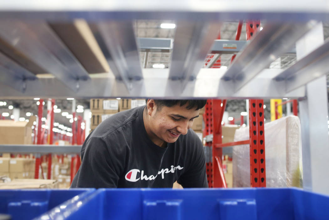 Warehouse associate assistant Enrique Roman prepares individual products to be sorted at the Se ...