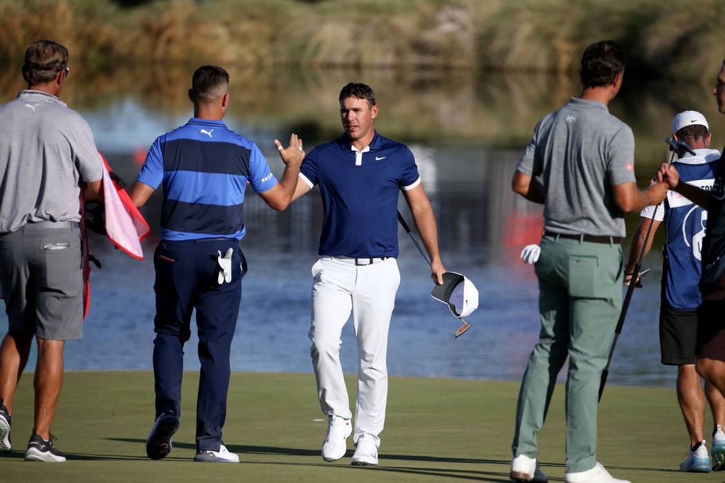 Brooks Koepka shakes hands with Gary Woodland after finishing up on the 18th hole during second ...
