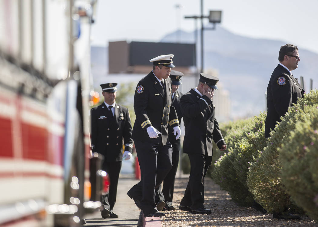Henderson Fire and Police Department personnel make their way into Central Church to honor the ...