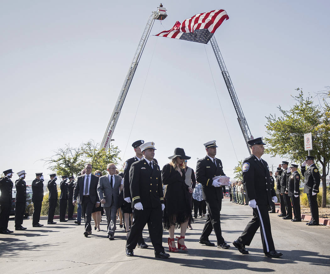 Henderson Fire Captain Garrett Dodrill, second from right, holds the urn containing the cremate ...