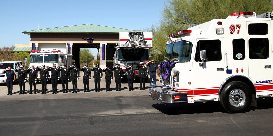 Firefighters stand outside of the Henderson Fire Station 97 in Henderson to watch the funeral p ...