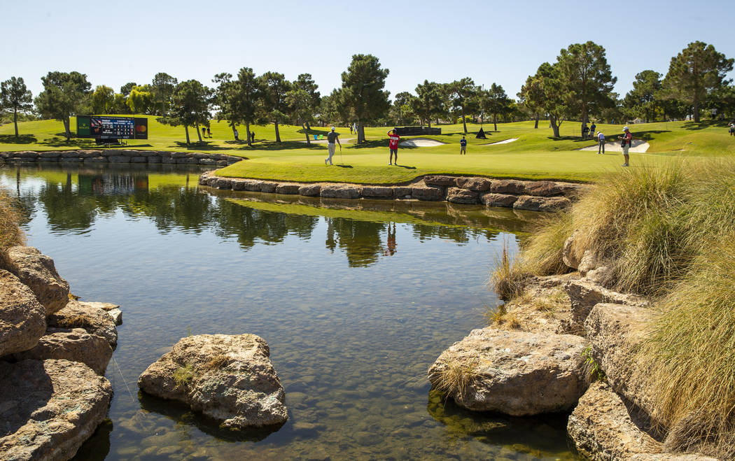 Golfers putt on the 16th green about the water hole during the third round of Shriners Hospital ...