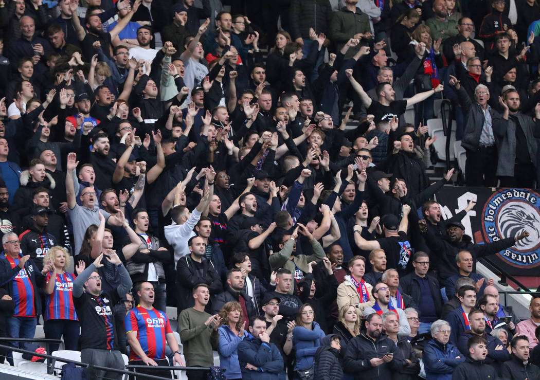 Fans cheer during a soccer match between the West Ham United and the Crystal Palace during the ...