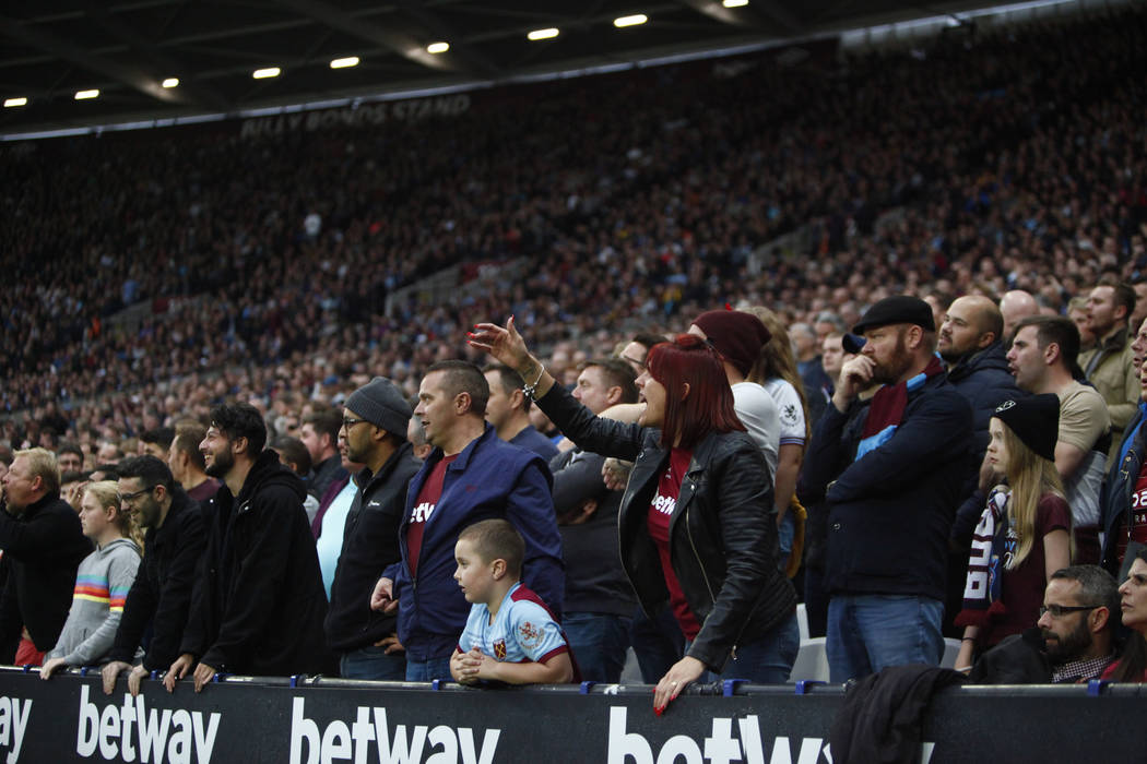 Fans react to a play during the first half of an English Premier League soccer match between th ...