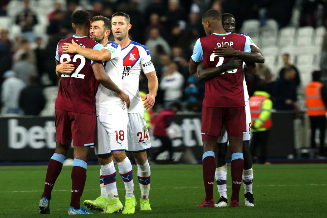Crystal Palace midfielder James McArthur (18) embraces West Ham United forward Sebastien Haller ...