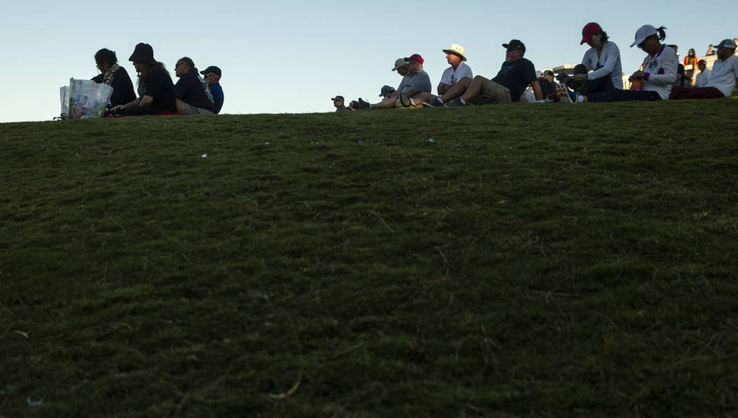 Gallery members sit in the setting sunlight about hole 18 during the third round of Shriners Ho ...