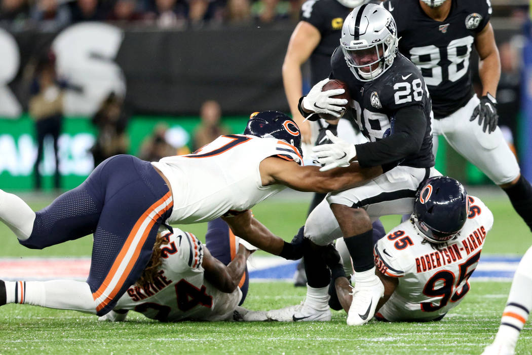 Oakland Raiders running back Josh Jacobs (28) is tackled by Chicago Bears defensive end Roy Rob ...