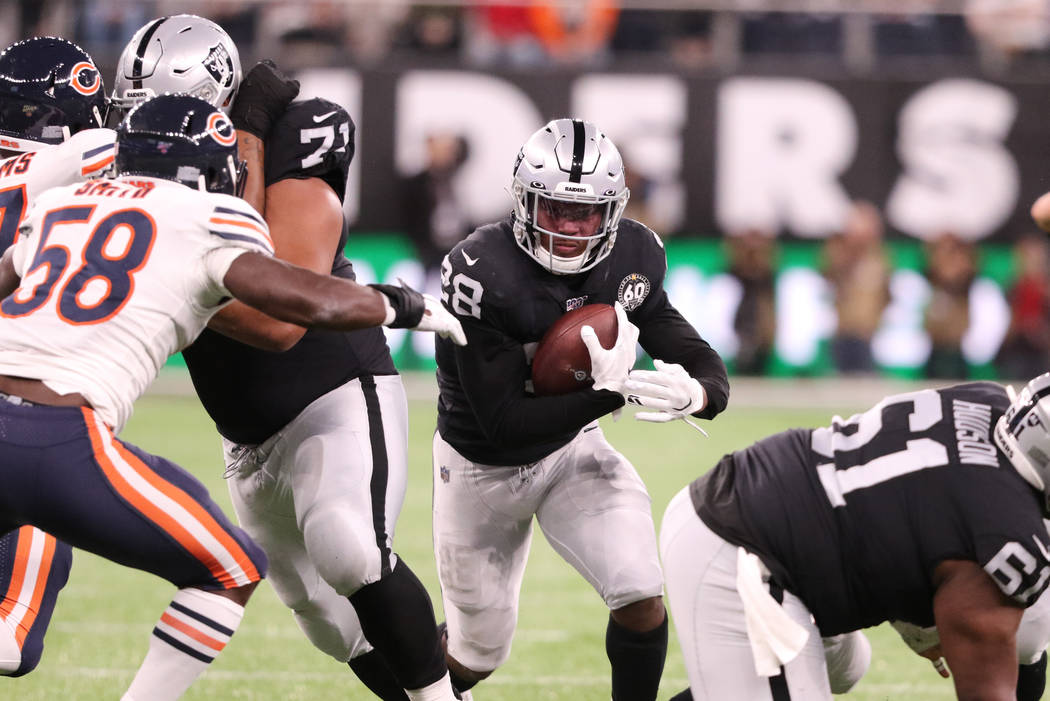 Oakland Raiders running back Josh Jacobs (28) runs with the football during the first half of a ...